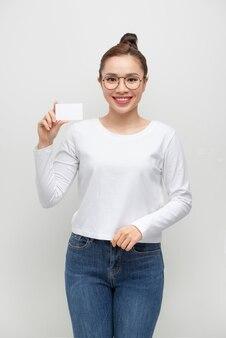 Jovem sorridente mostra cartão em branco. retrato de menina isolado na parede branca.