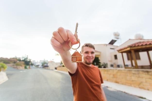 Jovem sorridente mostrando as chaves do novo apartamento imobiliário e o conceito de pessoas