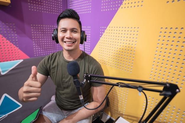 Jovem sorridente mostrando o polegar enquanto grava o podcast