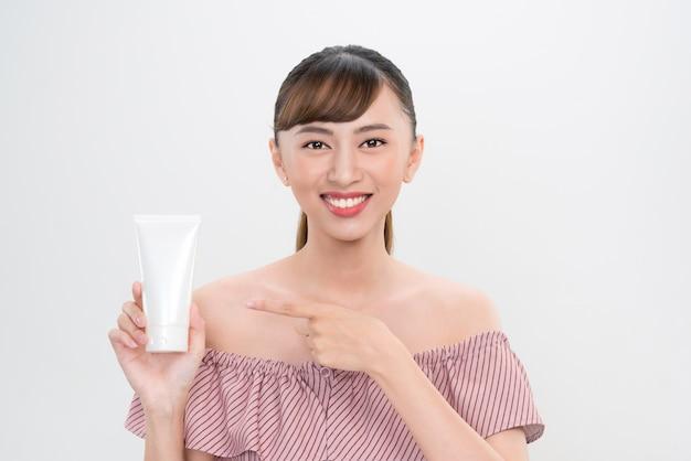 Jovem sorridente mostrando produtos para a pele