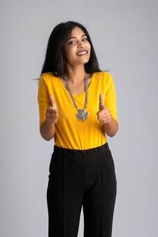 Jovem sorridente mostrando sinal de ok ou polegar para cima em um cinza