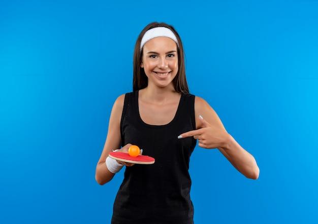 Jovem sorridente, muito esportiva, usando bandana e pulseira, raquete de pingue-pongue com uma bola e apontando para ela no espaço azul