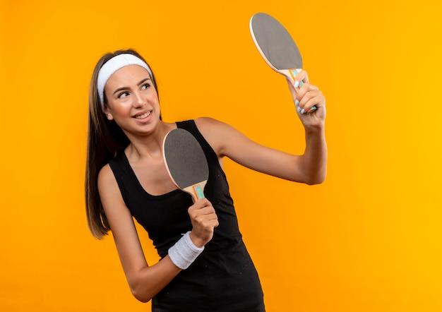 Jovem sorridente, muito esportiva, usando bandana e pulseira, segurando raquetes de pingue-pongue e olhando para o lado isolado no espaço laranja