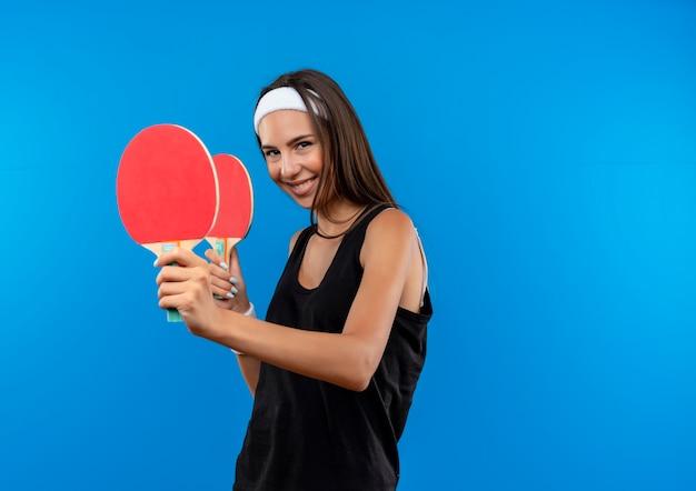 Jovem sorridente, muito esportiva, usando bandana e pulseira, segurando raquetes de pingue-pongue isoladas no espaço azul