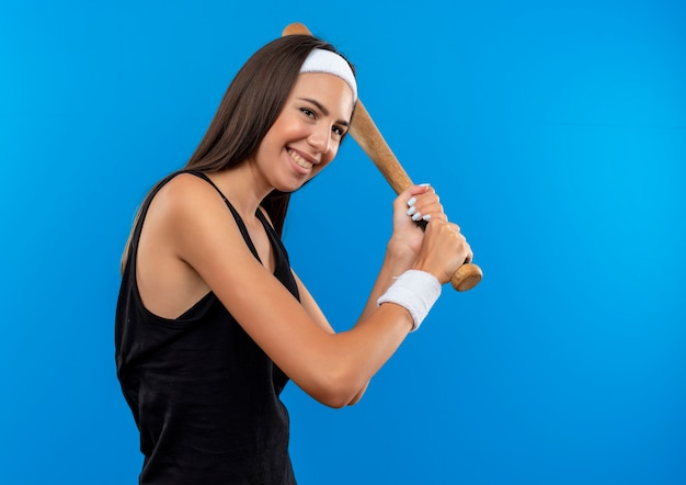 Jovem sorridente, muito esportiva, usando bandana e pulseira segurando um taco de beisebol isolado no espaço azul