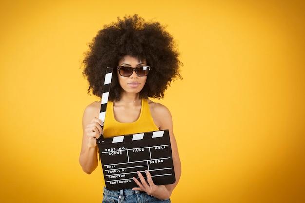 Jovem sorridente mulher afro-americana em uma calça casual posando isolado em um fundo de parede amarelo-laranja.