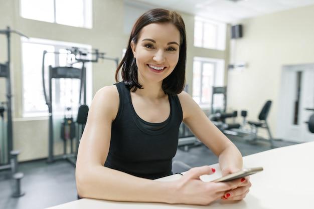 Jovem sorridente mulher atlética na academia com telefone móvel