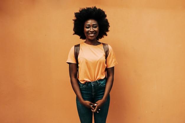 Jovem sorridente mulher atraente hipster africana em pé ao ar livre.