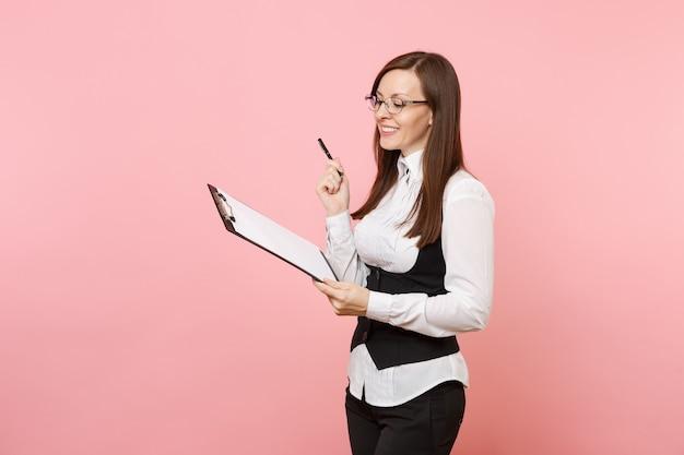 Jovem sorridente mulher de negócios bem-sucedida em copos segura o tablet da área de transferência com documentos de documentos isolado no fundo rosa. senhora chefe. conceito de riqueza de carreira de conquista. copie o espaço para anúncio.