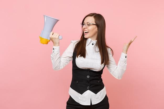 Jovem sorridente mulher de negócios em copos segurando um megafone, espalhando as mãos, olhando de lado isolado no fundo rosa pastel. senhora chefe. conceito de riqueza de carreira de conquista. copie o espaço para anúncio.