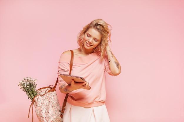 Jovem sorridente mulher estudante hipster com penteado rosa encaracolado colorido e tatuagem segurando o tablet