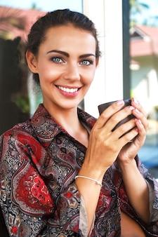 Jovem sorridente mulher muito positiva, bebendo seu café da manhã favorito, tem uma bela maquiagem natural e uma pele perfeita.