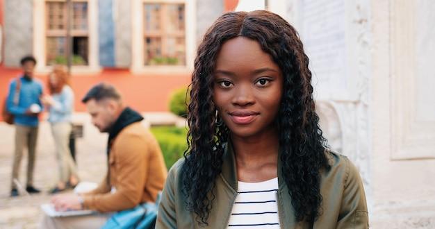 Jovem sorridente multirracial mulher vestindo roupas casuais, usando computador tablet ao ar livre na rua enquanto está sentado perto da parede e enviando mensagens. mo lento, steadicam