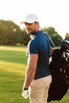 Jovem sorridente na tampa segurando o saco de golfe