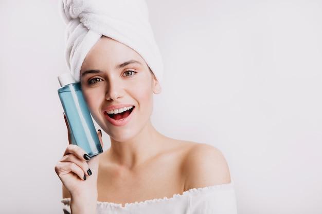 Jovem sorridente na toalha demonstra o tônico hidratante no frasco azul. retrato da modelo de olhos verdes sem maquiagem.