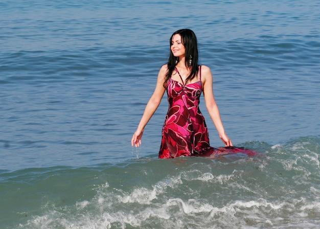 Jovem sorridente nas ondas do mar