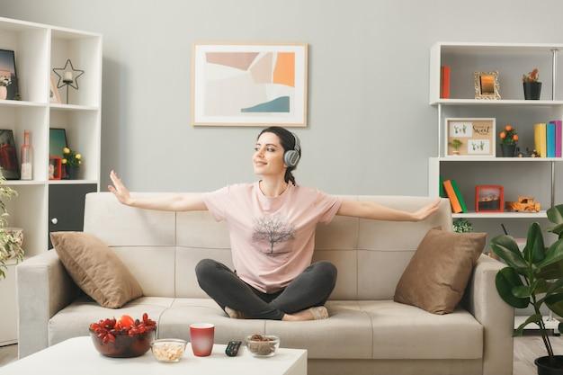 Jovem sorridente, olhando de lado, usando fones de ouvido, fazendo ioga, sentada no sofá atrás da mesa de centro na sala de estar