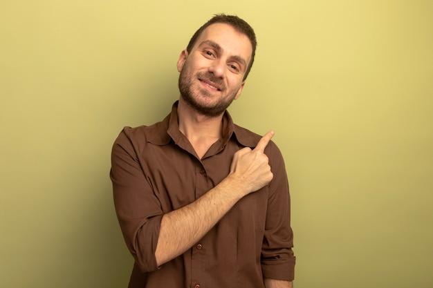 Jovem sorridente, olhando para a frente, apontando para o lado isolado na parede verde oliva