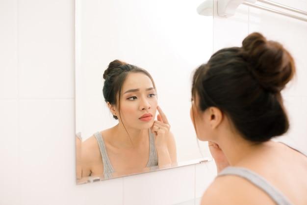 Jovem sorridente olhando para o espelho no banheiro de casa