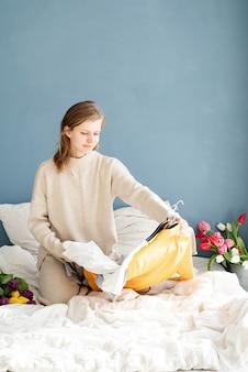 Jovem sorridente organizando roupas, sentada na cama em casa