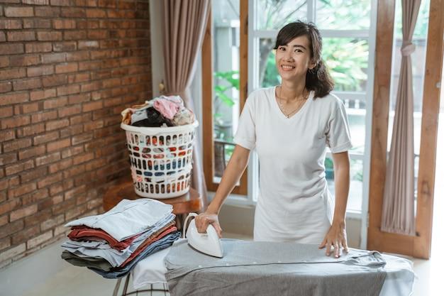 Jovem sorridente passando roupas em casa