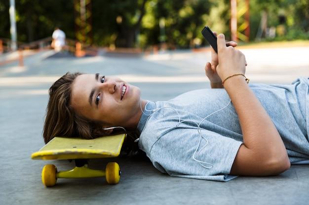 Jovem sorridente passando um tempo no parque de skate, ouvindo música com fones de ouvido, deitado no skate, segurando um telefone celular