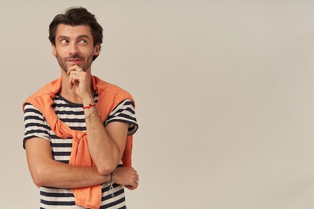 Jovem sorridente pensativo com a barba por fazer em camiseta listrada e suéter sobre os ombros pensando e olhando para o lado