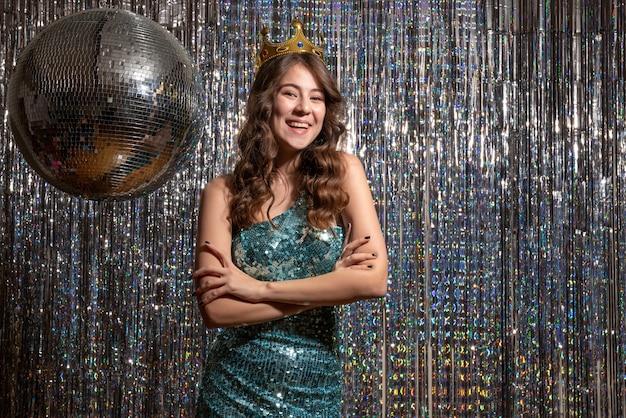Jovem sorridente, positiva e encantadora com vestido azul verde brilhante com lantejoulas e coroa na festa