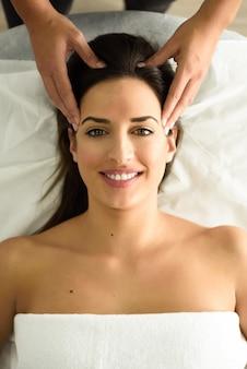 Jovem sorridente que recebe uma massagem na cabeça em um centro de spa.
