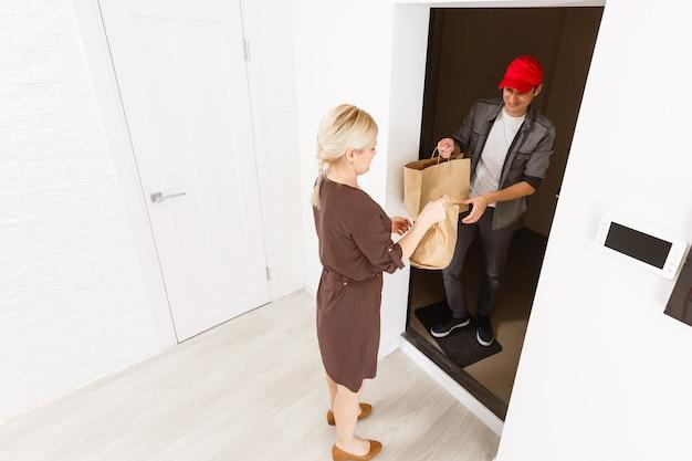 Jovem sorridente recebendo mantimentos do entregador em casa
