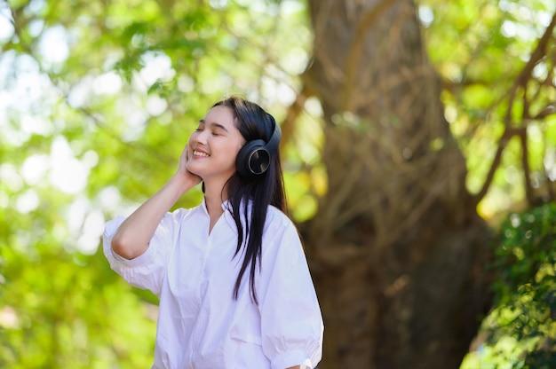 Jovem sorridente relaxando e ouvindo música com fones de ouvido Foto Premium