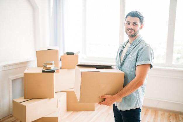 Jovem sorridente segura a caixa nas mãos, inauguração de casa. mudança para uma nova casa