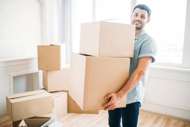 Jovem sorridente segura caixas de papelão nas mãos, inauguração de casa. mudança para uma nova casa