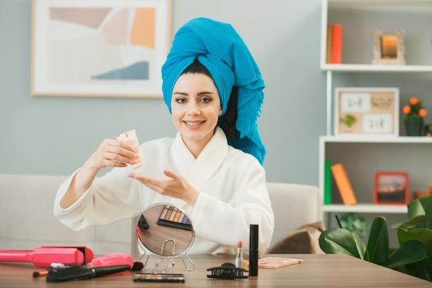 Jovem sorridente segurando creme de tonificação enrolado em uma toalha, sentada à mesa com ferramentas de maquiagem na sala de estar