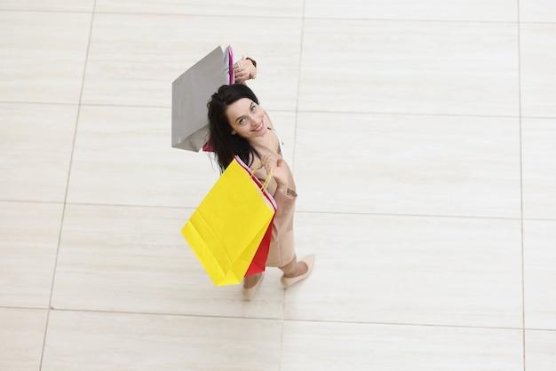 Jovem sorridente segurando muitos sacos de papel coloridos nas mãos e olhando para cima