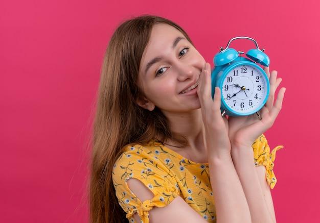 Jovem sorridente segurando o despertador na parede rosa isolada