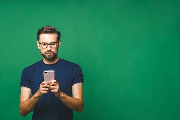 Jovem sorridente segurando o telefone inteligente e olhando para ele. retrato de um homem feliz que usa o telefone móvel isolado sobre o fundo verde.