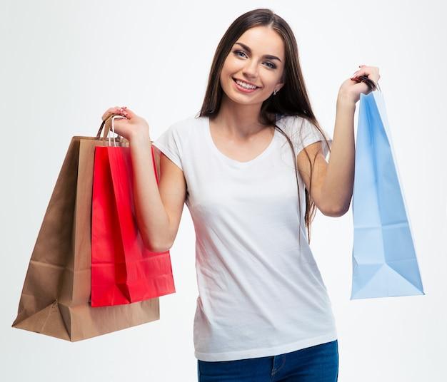 Jovem sorridente segurando sacolas de compras