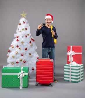 Jovem sorridente segurando um cartão em pé perto da árvore de natal em cinza