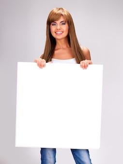 Jovem sorridente segurando um grande cartaz branco posando