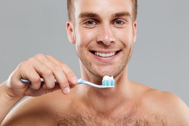 Jovem sorridente segurando uma escova de dentes com pasta de dente e limpando os dentes