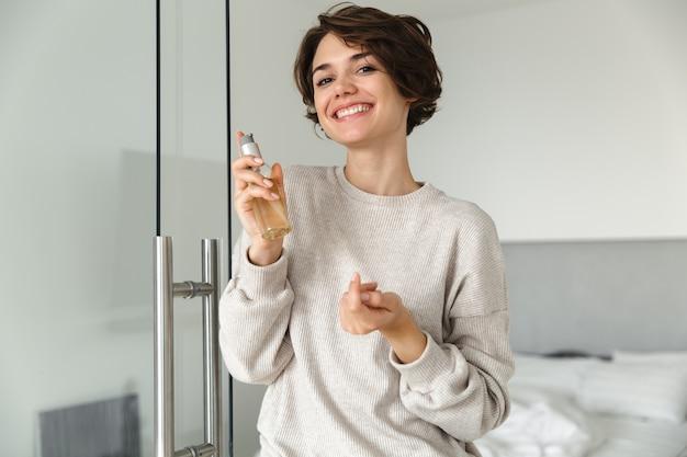Jovem sorridente segurando uma garrafa com loção de óleo no quarto