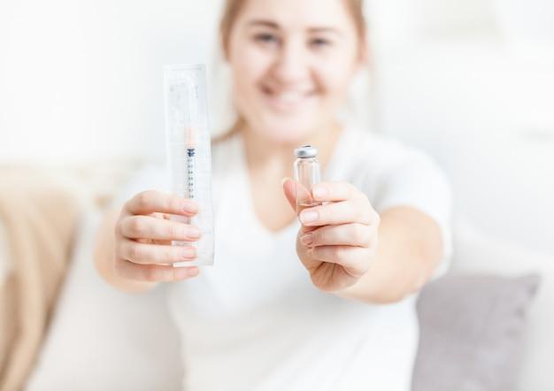 Jovem sorridente segurando uma seringa de insulina