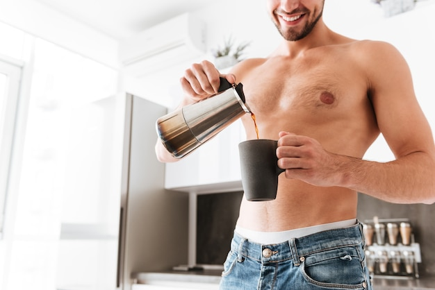 Jovem sorridente, sem camisa, de pé, servindo café na xícara na cozinha