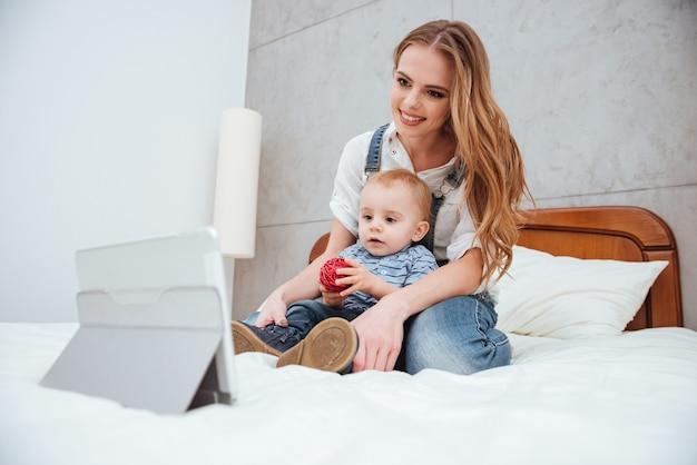 Jovem sorridente, sentada com o filho na cama, assistindo desenhos animados no tablet