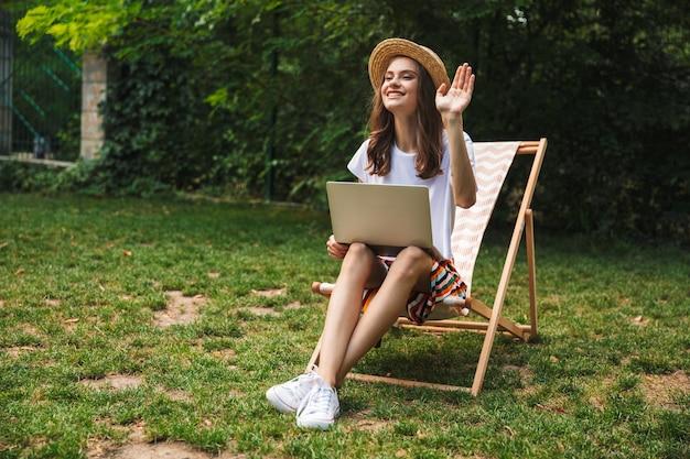 Jovem sorridente sentada com um laptop no parque ao ar livre, acenando com a mão