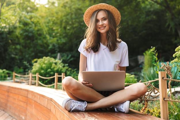 Jovem sorridente sentada com um laptop no parque ao ar livre