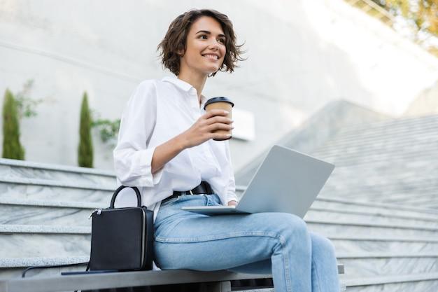 Jovem sorridente sentada no banco ao ar livre