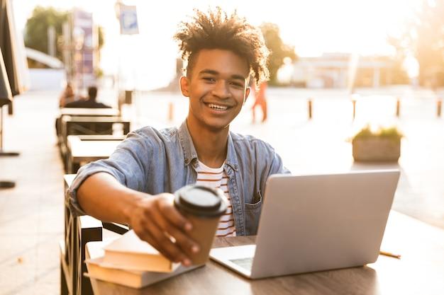 Jovem sorridente sentado no café ao ar livre