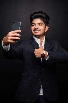 Jovem sorridente tirando foto de selfie em smartphone